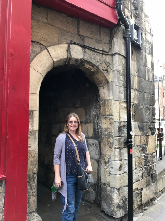 Me (Selina) posing in a stone archway - York