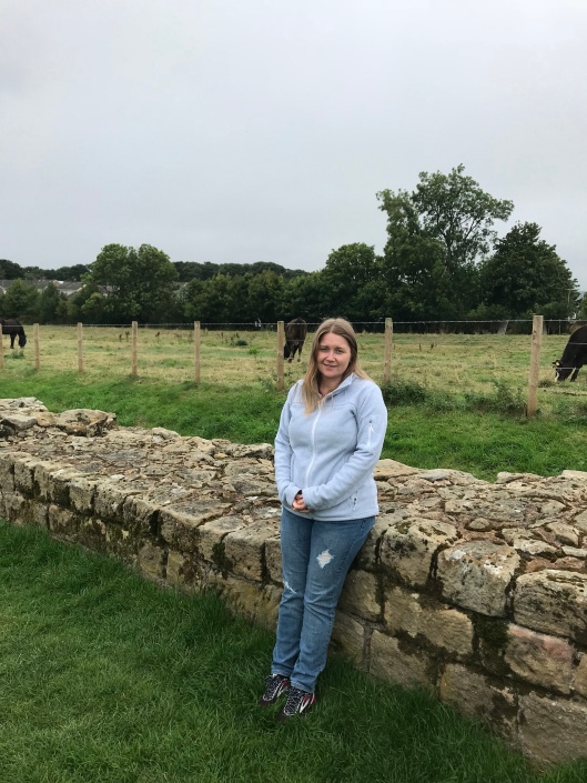 Me leaning against Hadrian's Wall - it was cold and sleeting rain that day.